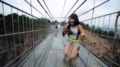 A glass bridge shatters under a tourist